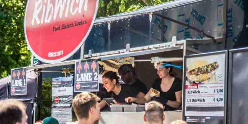 Mitarbeiter reichen Sandwiches aus dem Foodtruck Ribwich