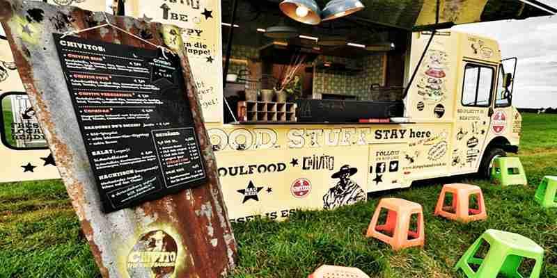 Foodtruck Chivito auf Wiese mit Sitzhockern und Speisekarte