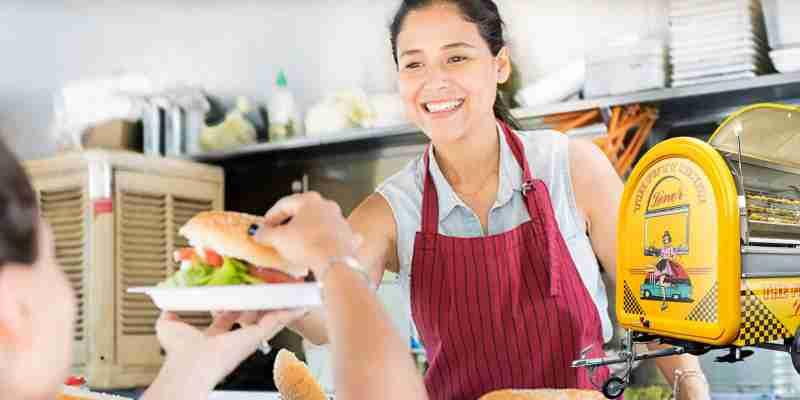 Foodtrailer BUDDYStar Frau reicht Burger an Kunden